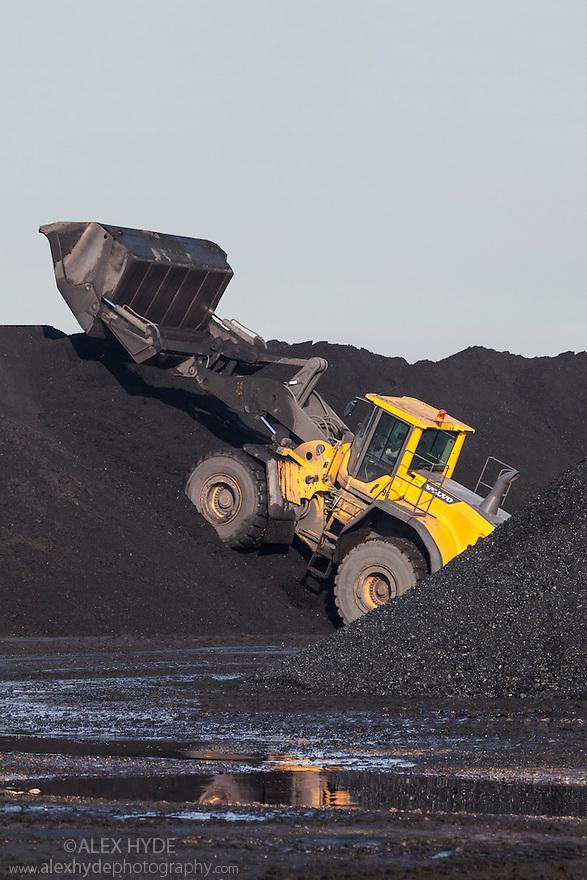 Digger moving coal between heaps. Yorkshire, UK.