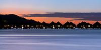 Sunset on lit-up overwater bungalows in Bora Bora lagoon, a romantic, luxury honeymoon destination, near Tahiti, French Polynesia, Pacific Ocean