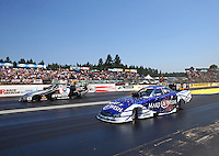 Aug. 3, 2014; Kent, WA, USA; NHRA funny car driver Tommy Johnson Jr (near lane) races alongside Jack Beckman during the Northwest Nationals at Pacific Raceways. Mandatory Credit: Mark J. Rebilas-