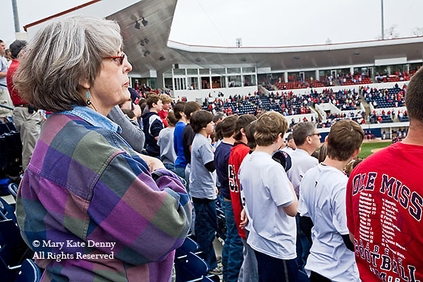 One gray haired senior female puts hand over heart for national anthem along with other fans in stadium as University Of Mississippi, Oxford, baseball game begins.