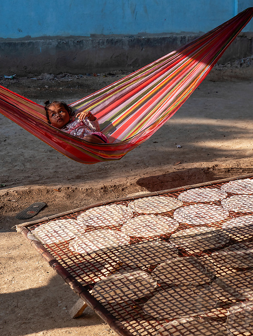 Traditional Rice paper production along the rural roads near Battambang is usually done by local families, Battambang. Rice paper is used for making the famous and delicious spring rolls. A child in a hanging mat