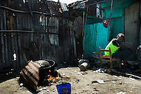A Haitian boy prepares food on the fire in the slum of Cité Soleil, Port-au-Prince, Haiti, 11 July 2008. Cité Soleil is considered one of the worst slums in the Americas, most of its 300.000 residents live in extreme poverty. Children and single mothers predominate in the population. Social and living conditions in the slum are a human tragedy. There is no running water, no sewers and no electricity. Public services virtually do not exist - there are no stores, no hospitals or schools, no urban infrastructure. In spite of this fact, a rent must be payed even in all shacks made from rusty metal sheets. Infectious diseases are widely spread as garbage disposal does not exist in Cité Soleil. Violence is common, armed gangs operate throughout the slum.