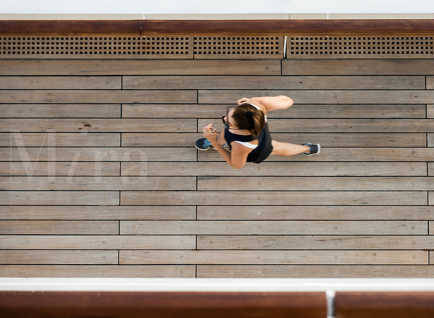 Woman jogging on the deck of a cruise ship.