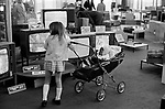 Multi ethnic Britain 1970s, white girls pushing black British baby in a pram around a department store London 1972