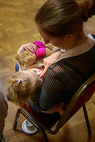 """A mother breastfeeding her toddler at a conference.<br /> <br /> Image from the breastfeeding collection of the """"We Do It In Public"""" documentary photography picture library project: <br />  www.breastfeedinginpublic.co.uk<br /> <br /> <br /> Middlesex, England, UK<br /> 2016<br /> <br /> © Paul Carter / wdiip.co.uk"""