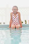 USA, Florida, St. Petersburg, Portrait of smiling girl (10-11) sitting in swimming pool