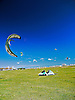 Kiteboarding is a surface water sport combining aspects of wakeboarding, snowboarding, windsurfing, surfing, paragliding, skateboarding and gymnastics into one extreme sport. A kiteboarder harnesses the power of the wind with a large controllable power kite to be propelled across the water on a kiteboard similar to a wakeboard or a small surfboard, with or without footstraps or bindings.<br />