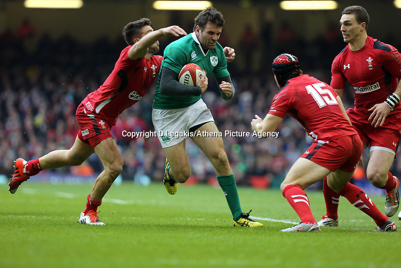 Pictured: Jared Payne of Ireland (C) is grabbed by Rhys Webb (L) and Leigh Halfpenny of Wales Saturday 14 March 2015<br /> Re: RBS Six Nations, Wales v Ireland at the Millennium Stadium, Cardiff, south Wales, UK.