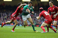 Pictured: Jared Payne of Ireland (C) is grabbed by Rhys Webb (L) and Leigh Halfpenny of Wales Saturday 14 March 2015<br />