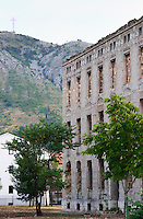 Building in Mostar damaged by the war and still not renovated. Ruined by bullet holes, mortar bomb shell grenade damage, very close to the beautifully renovated old town city centre. View of a hill with a cross on the top of the hill. The Third Primary School building along Ante Starcevica street. Town of Mostar. Federation Bosne i Hercegovine. Bosnia Herzegovina, Europe.