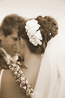 Sepia toned photo close up of flower in brides hair with groom in the backround
