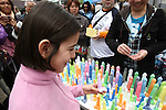 Apr 04, 2010 - Kawasaki, Japan - A woman look at phallus-shaped candles displayed for sale at the Kanamara Matsuri (Festival of the Steel Phallus) held in Wakamiya Hachimangu Shrine on April 4, 2010 in Kawasaki, Japan. The annual feritility festival, held traditionally the first Sunday in April, is said to encourage fertility and bring harmony to married couples. The festival has also become somewhat of a tourist attraction and is used to raise money for HIV research and awareness of AIDS prevention.