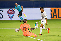 CARSON, CA - OCTOBER 07: Efrain Alvarez #26 of the Los Angeles Galaxy moves chips a shot over Steve Clark #12 GK of the Portland Timbers during a game between Portland Timbers and Los Angeles Galaxy at Dignity Heath Sports Park on October 07, 2020 in Carson, California.