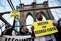 NEW YORK, USA - May 25: Black Lives Matteren supporters hold placards on the Brooklyn Bridge on the first anniversary of death on May 25, 2021 in New York City. George Floyd's assassination in Minneapolis sparked a worldwide outcry and continued to propel the Black Lives Matter movement through different cities in the United States and the world. (Photo by Pablo Monsalve / VIEWpress via Getty Images)