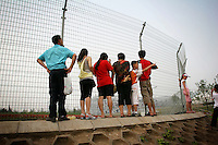 """CHINA. Beijing. People look through a fence, trying to catch a glimpse of the new Olympic park. In recent years construction has boomed in Beijing as a result of the country's widespread economic growth and the awarding of the 2008 Summer Olympics to the city. For Beijing's residents however, it seems as their city is continually under construction with old neighborhoods regularly being razed and new apartments, office blocks and sports venues appearing in their place. A new Beijing has been promised to the people to act as a showcase to the world for the 'new' China. Beijing's residents have been waiting for this promised change for years and are still waiting, asking the question """"Where's the new Beijing?!"""". 2008."""