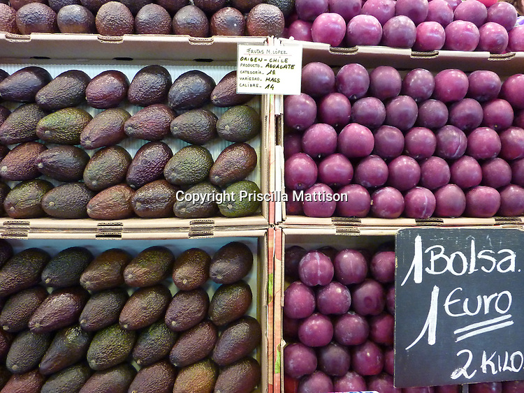 Avocadoes and plums are carefully stacked in boxes.