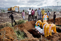 Relatives attend the funeral, at the King Tom cemetery, of a person who is suspected to have died from ebola. Due to the rapid increase in burials the cemetery is being enlarged and parts of a nearby rubbish dump is also being used to bury the dead.