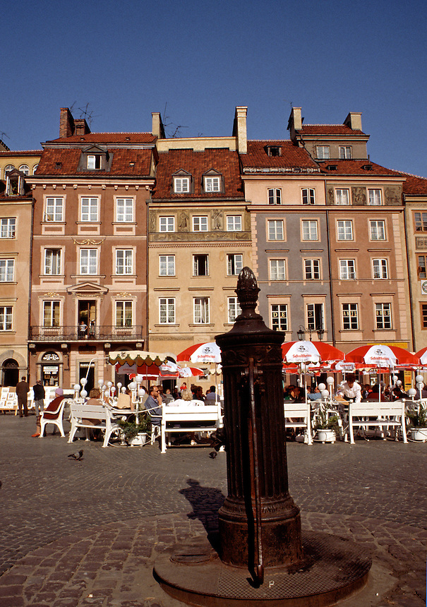 A water pump, buildings and outdoor cafe in the old town plaza of Warsaw. Poland.