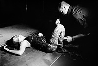 """Switzerland. Canton Ticino. Lugano. Couple and bondage. Bondage or ligotage is consentually tying, binding, or restraining a partner for erotic, aesthetic, and/or somatosensory stimulation. Rope, cuffs, bondage tape, self-adhesive bandages, or other restraints may be used for this purpose. Bondage itself does not imply sadomasochism. Bondage may be used as an end into itself, as in the case of rope bondage and breast bondage. It may also be used as a part of sex or in conjunction with other BDSM activities. The letter """"B"""" in the acronym """"BDSM"""" comes from the word """"bondage"""". Sexuality and erotica are an important aspect in bondage, but are often not the end in itself. Aesthetics also plays an important role in bondage. A common reason for the active partner to tie up their partner is so both may gain pleasure from the restrained partner's submission and the feeling of the temporary transfer of control and power. For sadomasochistic people, bondage is often used as a means to an end, where the restrained partner is more accessible to other sadomasochistic behaviour. However, bondage can also be used for its own sake. The active partner can derive visual pleasure from seeing their partner tied up, and the restrained partner can derive tactile pleasure from the feeling of helplessness and immobility. Extasia 2014 is the first erotic and sex fair in southern Switzerland. 1.02.14 © 2014 Didier Ruef"""