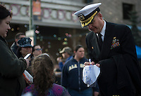 130501-N-DR144-281 ANCHORAGE, Alaska (May 1, 2013)- Cmdr. Joel Stewart, commanding officer of San Antonio-class amphibious transport dock ship USS Anchorage (LPD 23) signs a white hat for a child at the Dock on the Block party in downtown Anchorage. The city of Anchorage and various sponsors provided free food, rides and entertainment for Sailors and their families along 6th Avenue. Anchorage is currently moored in its namesake city of Anchorage, Alaska for its commissioning ceremony scheduled to take place May 4. (U.S. Navy photo by Mass Communication Specialist 1st Class James R. Evans / RELEASED)