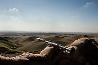 A rocket launcher belonging to Peshmerga soldiers on the frontline in Kirkuk rests on sand bags overlooking Iraqi army positions in the valley below.