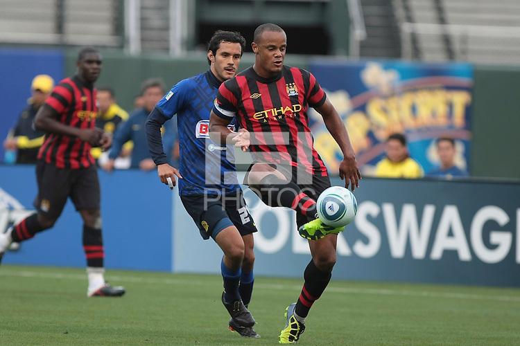 Vincent Kompany (right) controls the ball ahead of Daniel Marquez (left). Manchester City defeated Club America 2-0 in the Herbalife World Football Challenge 2011 at AT&T Park in San Francisco, California on July 16th, 2011.