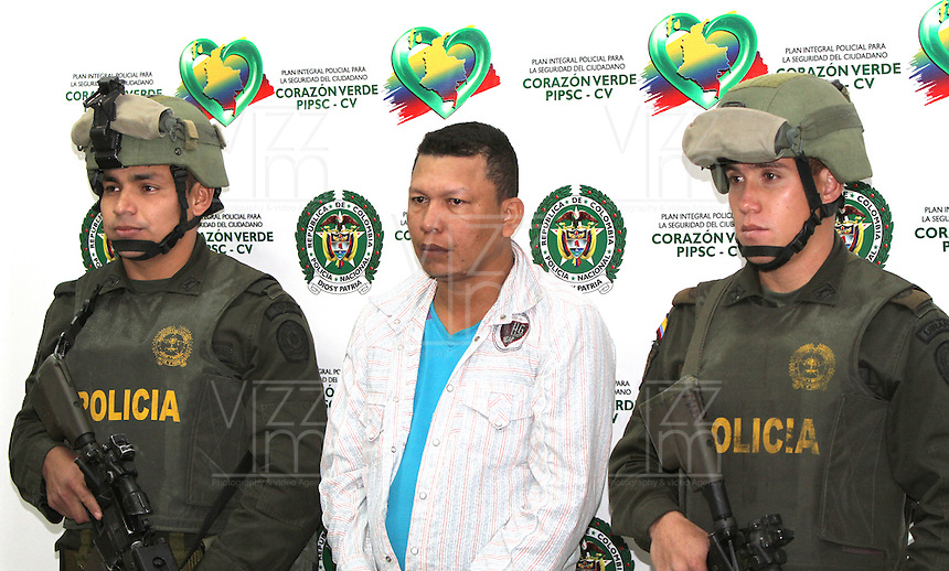 "BOGOTA -COLOMBIA, 26 -07-2013.  Miembros de la Policia Nacional de Colombia custodian a Hernán Arturo Cantillo Camargo ,alias "" Yovanny"" principal detractor de la Ley de víctimas y restitución de tierras en la costa Atlántica,sindicado del 75% de los desplazamientos forzados en la Costa Caribe ,generó la migración de más de 28 mil personas ,participó en una incursión armada donde fueron acribilladas 36 personas.Base antinarcóticos de La Policia Nacional de Colombia, Members of the National Police of Colombia guarding Cantillo Hernán Arturo Camargo, alias ""Yovanny"" principal opponent of the Act of victims and land restitution on the Atlantic coast, accused the 75% of forced displacement on the Caribbean coast, generated migration over 28 thousand people took part in an armed raid where 36 were shot counternarcotics personas.Base The National Police of Colombia. <br /> . Photo: VizzorImage/ Felipe Caicedo/ STAFF"