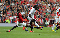 Pictured: Bafetimbi Gomis of Swansea (R) against Tyler Blackett of Manchester United (L). Saturday 16 August 2014<br />