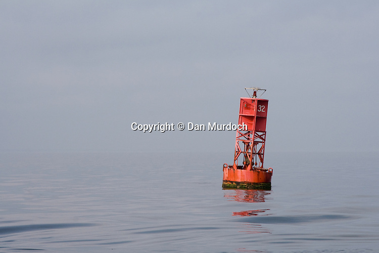 Red buoy 32 on quiet water in the morning light