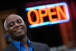 African American man in business suit without tie in front of open sign