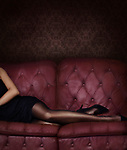 Closeup of sexy legs in black stocking of a woman lying on a luxurious pink red tufted couch wearing a short black dress and high heel shoes Image © MaximImages, License at https://www.maximimages.com