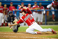 Batavia Muckdogs shortstop Anthony Melchionda #16 does a hook slide to avoid the tag of a diving Connecticut Tigers catcher Bennett Pickar #14 to score the game winning run in the bottom of the 9th inning on a base hit by Jacob Wilson #32 (not pictured) during a NY-Penn League game at Dwyer Stadium on July 4, 2012 in Batavia, New York.  Batavia defeated Connecticut 3-2.  (Mike Janes/Four Seam Images)