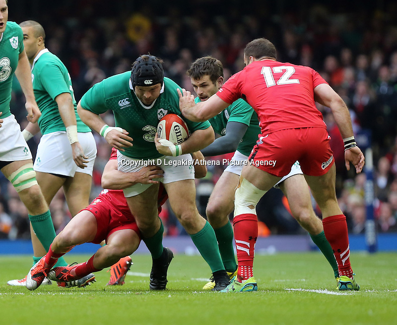Pictured: Mike Ross of Ireland (L) is brought down by Rhys Webb and Jamie Roberts (12) of Wales Saturday 14 March 2015<br /> Re: RBS Six Nations, Wales v Ireland at the Millennium Stadium, Cardiff, south Wales, UK.