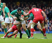 Pictured: Mike Ross of Ireland (L) is brought down by Rhys Webb and Jamie Roberts (12) of Wales Saturday 14 March 2015<br />