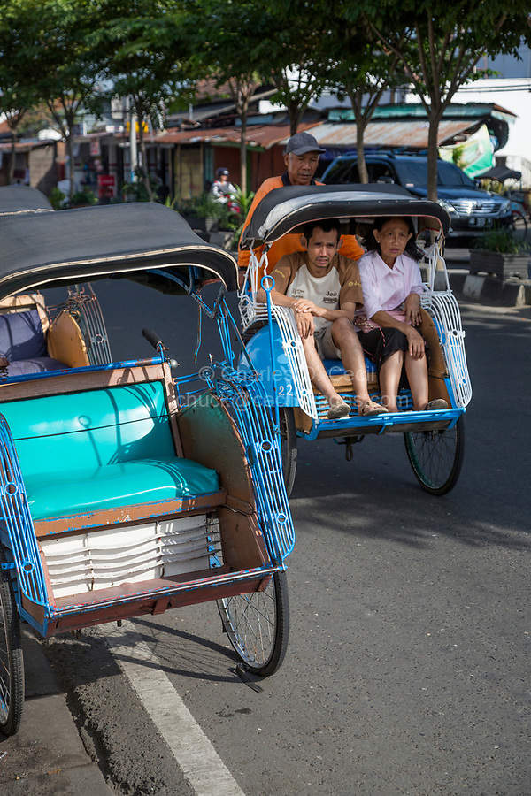 Yogyakarta, Java, Indonesia. Man and Woman Riding in a Becak, a Three-wheeled Vehicle Powered by Human Propulsion.  Jalan Malioboro Street.