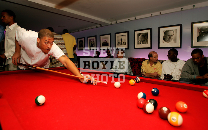 Michael Beasley plays pool at Jay Z's 40/40 Club while other players watch MTV's Video Music Awards on TV on August 31, 2006.  The high school players were in town for the Elite 24 Hoops Classic, which brought together the top 24 high school basketball players in the country regardless of class or sneaker affiliation.