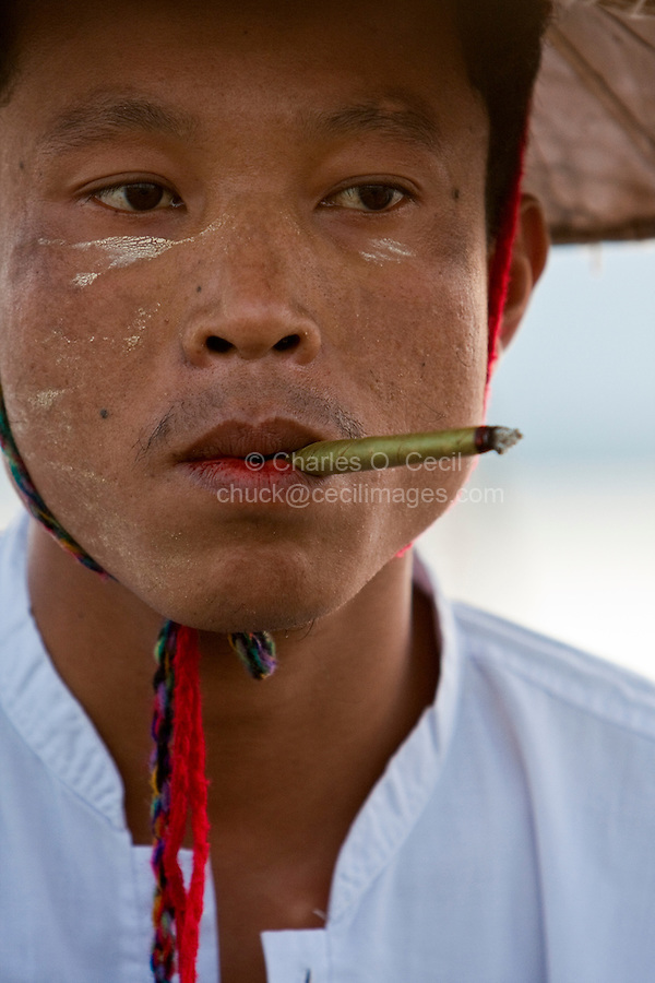 Myanmar, Burma.  Fisherman with Cheroot, Inle Lake, Shan State.  He has traces of thanaka paste on his face, a cosmetic sunscreen.