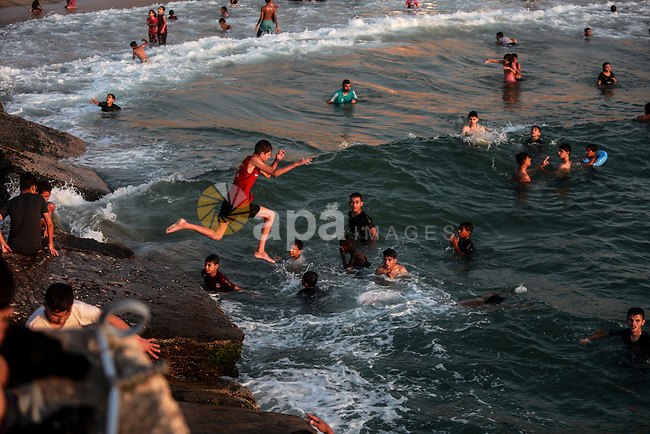 Palestinians enjoy their time at the beach of Gaza sea during a hot day on August 6, 2021. The beach is one of the few open public spaces in this densely populated city. Photo by Mohammed Dahman