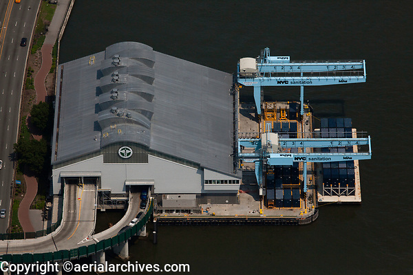 aerial photograph of the New York City Department of Sanitation Upper East Side Marine Transfer Station at East 91st Street in Manhattan, New York City; the Bobby Wagner Walk and FDR drive are at the right side of the photograph