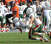 Oct 30, 2010; Charlottesville, VA, USA;  Virginia Cavaliers running back Perry Jones (33) is tackled by Miami Hurricanes linebacker Sean Spence (31) and Miami Hurricanes linebacker Colin McCarthy (44) during the game at Scott Stadium. Virginia won 24-19. Mandatory Credit: Andrew Shurtleff