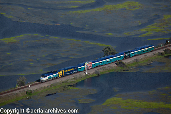 aerial photograph of the Coaster commuter train, San Diego, California, crossing the Los Penasquitos Lagoon,  San Diego County, California