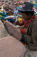 "Carving traditional prayer stones at Namtso Lake :Namtso, another holy lake in Tibet, is located near Damxung. 4718 meters (15475 feet) above sea level and covering 1900 square kilometers (735 square miles), the lake is the highest saltwater lake in the world and the second largest saltwater lake in China. The snow capped Mt. Nyainqentanglha, considered as the son of Namtso and leader of sacred mountains, soars up to sky beside her. Singing streams converge into the clean sapphire blue lake, which looks like a huge mirror framed and dotted with flowers..The Namtso Lake is held as ""the heavenly lake"" or ""the holy lake"" in northern Tibet. .Respected as one of the three holiest lakes in Tibet, the Namtso Lake is the seat of Paramasukha Chakrasamvara for Buddhist pilgrims. In the fifth and sixth month of the Tibetan calendar each year, many Buddhists come to the lake pay homage and pray. Deep tracks are worn into the lakeshore due to this activity. In history, monasteries stood like trees in a forest around the site, attracting large numbers of pilgrims as eminent monks in Buddhist temples extended Buddhist teachings...Buddhists believe Buddhas, Bodhisattvas and Vajras will assemble to hold religious meeting at Namtso in the year of sheep on Tibetan calendar. It is said that walking around the lake at the right moment is 100,000 times more efficacious than that in normal years. That's why thousands of pilgrims from every corner of the world come to pray at the site, with the activity reaching a climax on Tibetan April 15...Walking around the lake takes a week. Ritual walkers love to burn aromatic plants to raise smoke on Auspicious Island [explain this a little] and throw a piece of hada scarf into the lake as a token of fulfilled wishes. If the scarf sinks, it implies ones wish is accepted by the Buddha; if the scarf flows on the water or only half sinks, it means one has failed to be honest and something unhappy may lie ahead...On the four sides of the lake stand four"