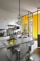 The contemporary kitchen has a concrete kitchen island above which hangs an antique crystal chandelier