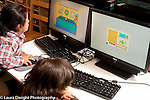 Education Preschool 3-4 year olds two children sitting side by side playing educational games on computers