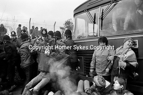 Greenham Common Womens Peace movement. Women stopping a bus with workers entering the military base. Police making arrests. December 1982 1980s UK