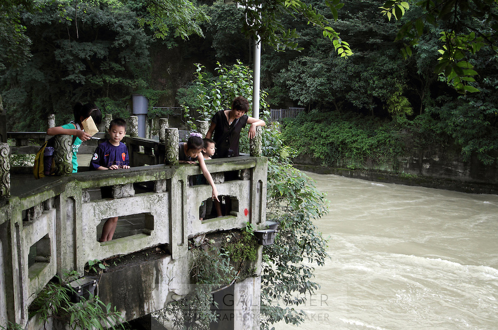 """A family visits the the Dujiangyan Irrigation System. The system is regarded as an """"ancient Chinese engineering marvel."""" By naturally channeling water from the Min River during times of flood, the irrigation system served to protect the local area from flooding and provide water to the Chengdu basin. Sichuan Province. 2010"""