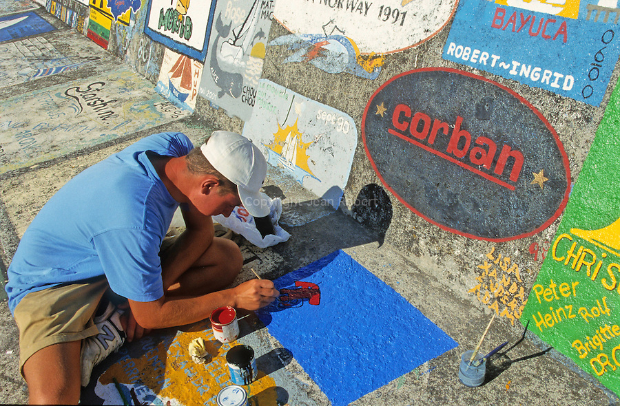 sailor painting a flag on the sidewalk of the marina's jetty of Horta.