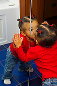 MR / Schenectady, NY. Infant (girl, 11 months, African American & Caucasian) kisses her reflection in the mirror. MR: Dal4. ID: AL-HD. © Ellen B. Senisi