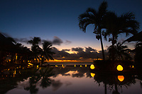 Colorful and romantic Indian Ocean sunset with palm trees and thatched roof bar silhouettes and lights reflecting on a pool, Mauritius Island, Africa