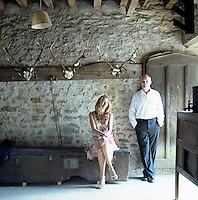 Lord and Lady Edward Manners in a stone barn that houses fishing rods and old hunting trophies
